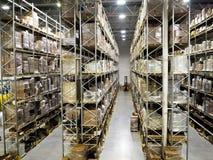 Большой современный запачканный склад промышленный и компании снабжения Вызванное складирование на поле и высокими полками стоковые изображения