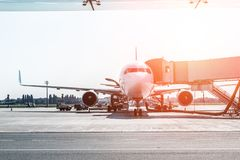 Большой современный коммерчески самолет на авиаполе состыкованном с мостом восхождения на борт на восходе солнца или заходе солнц стоковые фото