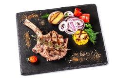 Большой стейк мяса на косточке, зажаренный, который служат с зажаренными овощами, мозоль, красный лук, сладкие перцы, картошки стоковое изображение rf