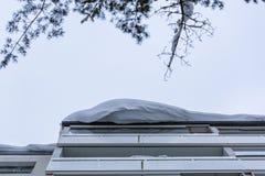 Большой сугроб на крыше жилого дома стоковое фото