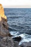 Большой утес на море захода солнца голубом и парусник в расстоянии стоковое изображение