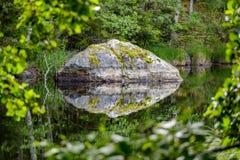 Большой утес отраженный в спокойной поверхности воды Стоковые Изображения