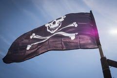 Большой флаг пирата развевая на ветре на предпосылке голубого неба Стоковые Изображения RF