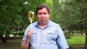 Большой человек держа золотой воздушный шар делая 0 номеров на открытом воздухе 0th партия торжества годовщины сток-видео