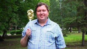 Большой человек держа золотой воздушный шар делая 8 номеров на открытом воздухе восьмая партия торжества годовщины сток-видео