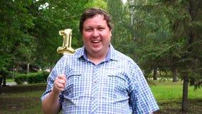 Большой человек держа золотой воздушный шар делая 1 номер на открытом воздухе 1th партия торжества годовщины сток-видео