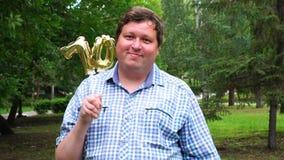 Большой человек держа золотые воздушные шары делая 70 номеров на открытом воздухе семидесятая партия торжества годовщины сток-видео