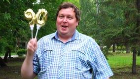 Большой человек держа золотые воздушные шары делая 90 номеров на открытом воздухе девятидесятая партия торжества годовщины видеоматериал