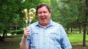Большой человек держа золотые воздушные шары делая 18 номеров на открытом воздухе восемнадцатая партия торжества годовщины сток-видео