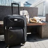 Большой чемодан катят чернотой, который стоя на поле в авиапорте, рюкзаке и плаще ` s женщины на стенде Стоковые Изображения RF