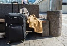 Большой чемодан катят чернотой, который стоя на поле в авиапорте, рюкзаке и плаще ` s женщины на стенде Стоковые Фотографии RF