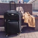 Большой чемодан катят чернотой, который стоя на поле в авиапорте, рюкзаке и плаще ` s женщины на стенде Стоковое Изображение RF