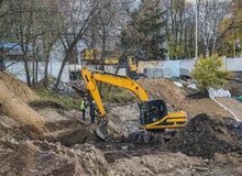Большой экскаватор во время earthmoving работ outdoors на строительной площадке Желтый экскаватор освобождает русло реки для пруд стоковые изображения rf