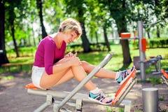 Боль чувства молодой женщины в ее колене во время разминки спорта в стоковые фото
