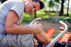 Боль чувства человека в его колене во время спорта и разминка в p стоковое фото rf