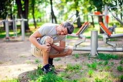 Боль чувства человека в его колене во время спорта и разминка в p стоковое изображение rf