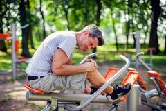 Боль чувства человека в его колене во время спорта и разминка в p стоковое фото
