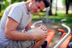 Боль чувства человека в его колене во время спорта и разминка в p стоковые фото