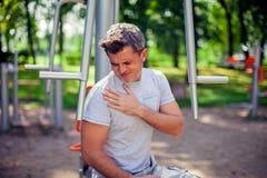 Боль чувства человека в его комоде во время спорта и разминка в стоковое фото