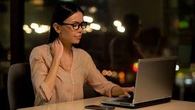Боль шеи уставшей дамы дела чувствуя работая на ноутбуке вечером, здравоохранение стоковая фотография rf