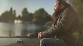 Бородатая рыбная ловля рыболова на речном береге Человек сидит с рыболовной удочкой outdoors Рыбная ловля реки сток-видео