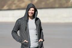 Бородатая улыбка в клобуке на солнечное внешнем, мода человека Мачо счастливый усмехаться в фуфайке, непринужденный стиль Мода лю Стоковые Изображения