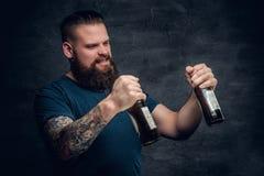 Бородатое мужское смотрящ 2 пустых пивной бутылки Стоковое Фото
