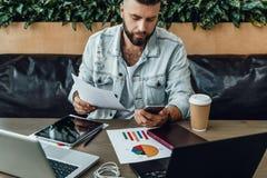 Бородатый бизнесмен битника работая с документами в современном офисе Человек использует smartphone, печатая сообщение на мобильн стоковое изображение rf