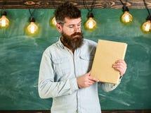 Бородатый битник держит книгу, доску на предпосылке Учитель в eyeglasses представляя пустую книгу словесность стоковые фотографии rf