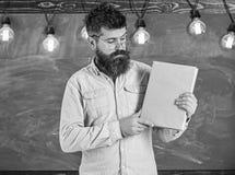 Бородатый битник держит книгу, доску на предпосылке Учитель в eyeglasses представляя пустую книгу словесность стоковая фотография rf
