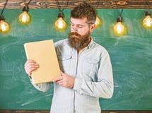 Бородатый битник держит книгу, доску на предпосылке Учитель в eyeglasses представляя пустую книгу словесность стоковое фото rf