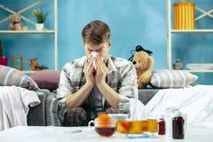 Бородатый больной человек с газоходом сидя на софе дома Болезнь, инфлуенза, концепция боли домашняя релаксация Здравоохранение стоковая фотография