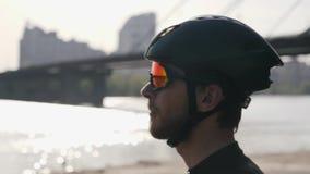 Бородатый велосипедист нося черный шлем и солнечные очки смотря сфокусированный к горизонту Река и мост на заднем плане Задейству сток-видео