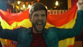 Бородатый вентилятор спорт развевая испанский флаг в пабе, радуясь победа национальной команды сток-видео