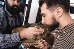 Бородатый винодел в рисберме дает к человеку в вдохе рубашки шотландки конусы хмеля в винзаводе стоковая фотография rf