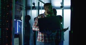 Бородатый инженер ИТ используя ноутбук в комнате сервера стоковая фотография rf