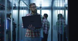 Бородатый инженер ИТ используя ноутбук в комнате сервера стоковая фотография