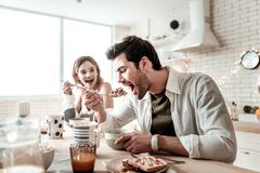 Бородатый красивый положительный человек в белой рубашке есть салат на завтрак стоковое изображение