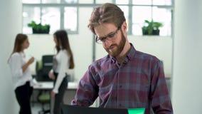 Бородатый менеджер проверяет информацию на его llaptop стоя в конце залы вверх видеоматериал