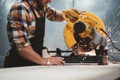 Бородатый механик работника используя электрический угловой шлифовальный станок в заводе механической обработки Работа в действии стоковое фото rf