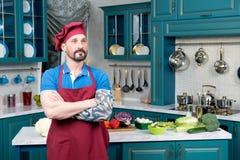Бородатый мечтая кашевар с татуированной и пересеченной рукой на кухне Стоковые Изображения RF