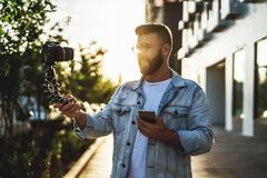 Бородатый мужской блоггер хипстера в ультрамодных стеклах стоя на улице города, держит камеру на блоге треноги и всходов видео- стоковое фото
