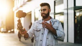 Бородатый мужской блоггер хипстера в ультрамодных стеклах стоя на улице города, держит камеру на блоге треноги и всходов видео- стоковое изображение rf