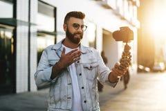 Бородатый мужской блоггер хипстера в ультрамодных стеклах стоя на улице города, держит камеру на блоге треноги и всходов видео- стоковые изображения rf