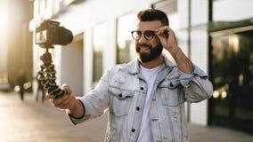 Бородатый мужской блоггер хипстера в ультрамодных стеклах стоя на улице города, держит камеру на блоге треноги и всходов видео- стоковое изображение