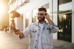 Бородатый мужской блоггер хипстера в ультрамодных стеклах стоя на улице города, держит камеру на блоге треноги и всходов видео- стоковые фотографии rf
