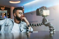Бородатый мужской видео- блоггер создает видео- содержание для его канала Vlogger человека сбрасывает на камере с треногой стоковая фотография rf