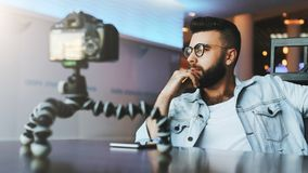 Бородатый мужской видео- блоггер создает видео- содержание для его канала Vlogger человека сбрасывает на камере с треногой стоковые изображения