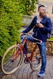 Бородатый мужчина в парке говорит умным телефоном стоковые изображения rf