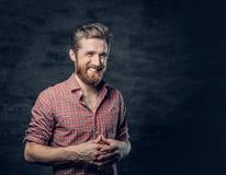 Бородатый мужчина одетый в красной рубашке ватки делает переговор стоковая фотография